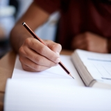 Closeup shot of a young man writing on a note pad
